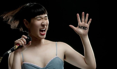 Woman with microphone yelling with Word written on hand