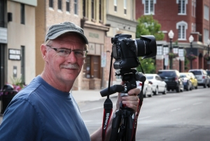 Man with camera and tripod on street