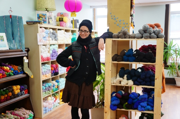 Woman in front of colourful wool display