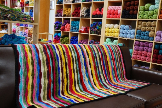 colourful yarn shop with leather couch and crocheted blanket