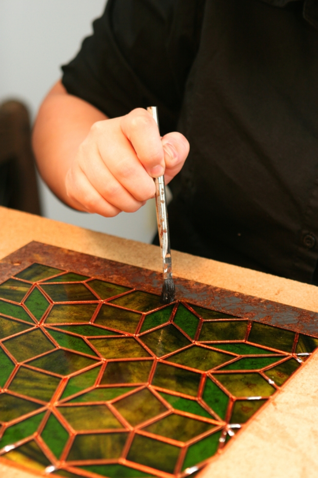 Woman holding brush working on stained glass project
