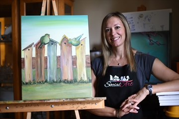 Woman standing beside painting on easel