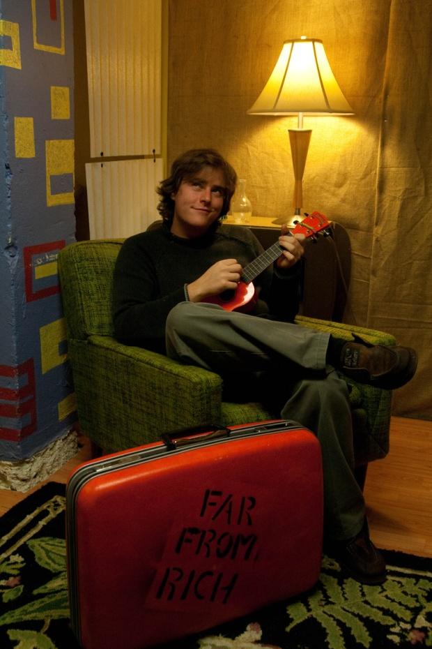 Man playing ukulele sitting in chair