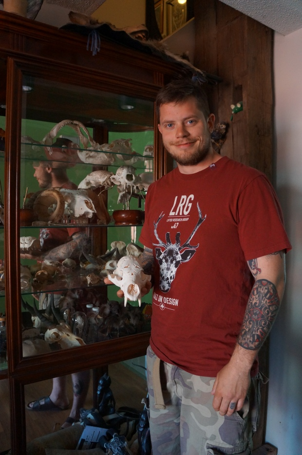 Man holding skull in front of cabinet filled with skulls