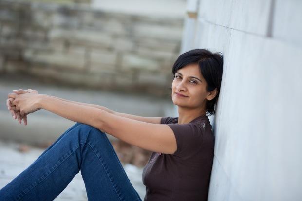 Canadian writer Tasneem Jamal sittingagainst a wall