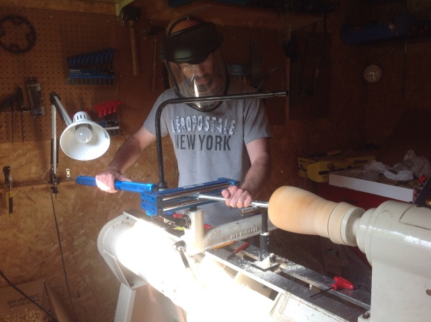 Man turning wood on lathe,