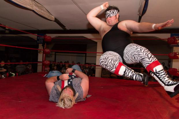 Wrestler in animal print tights  doing a move in the ring