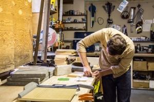 Man in garage studio making notebooks